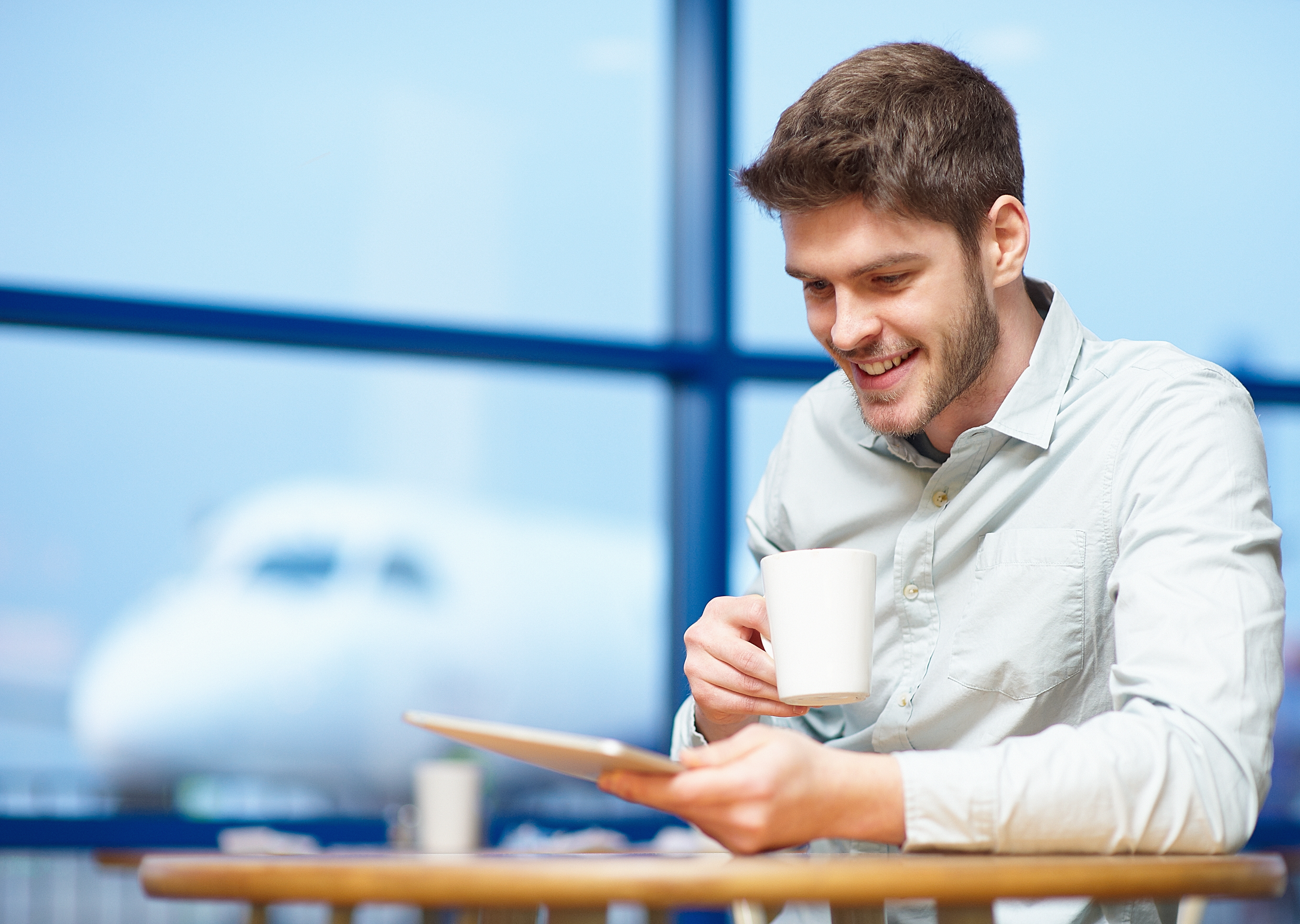 man-drinking-coffee-using-tablet-airport-4958 x 35